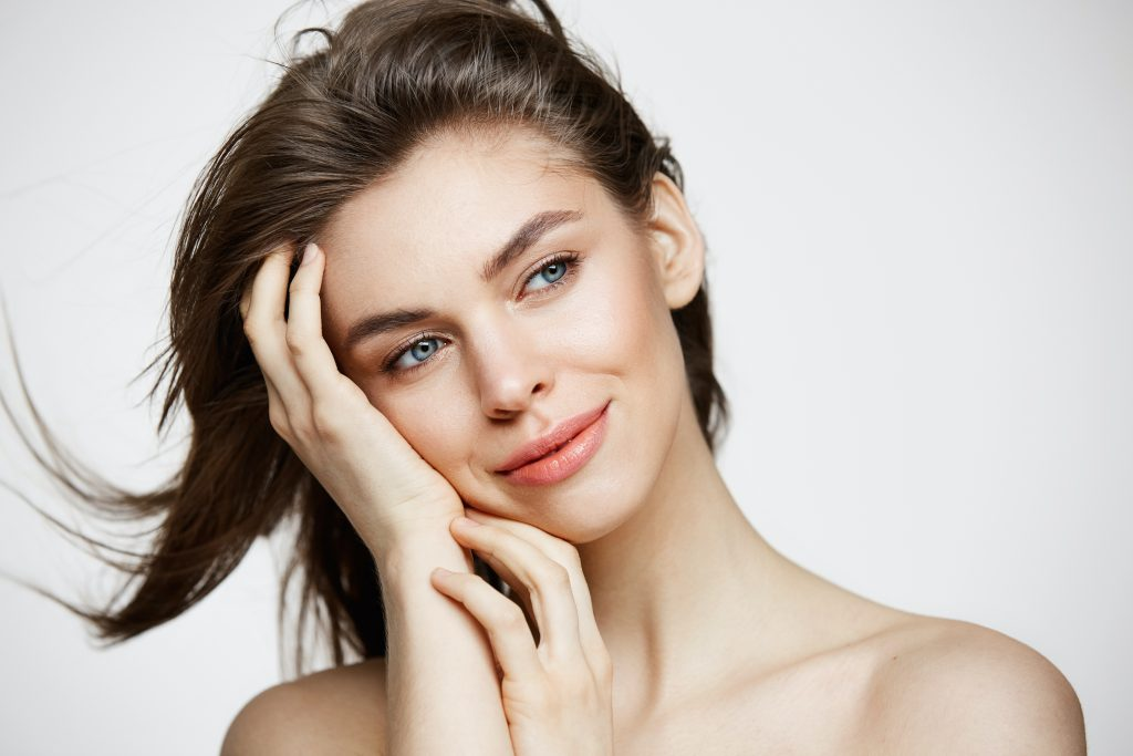 Model smiling with hand on face